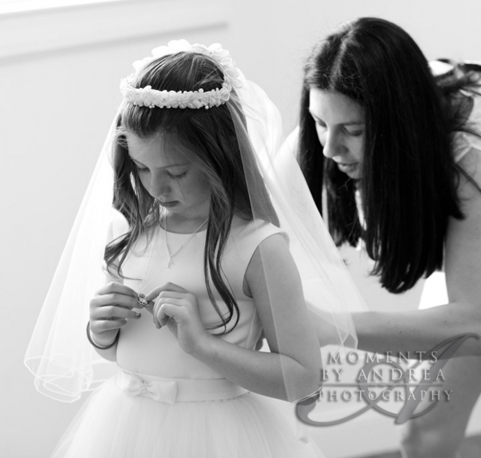 Mother preparing daughter for First Communion